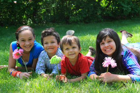 sibling: Four siblings consisting of two brothers and 2 sisters laying on the grass in the park
