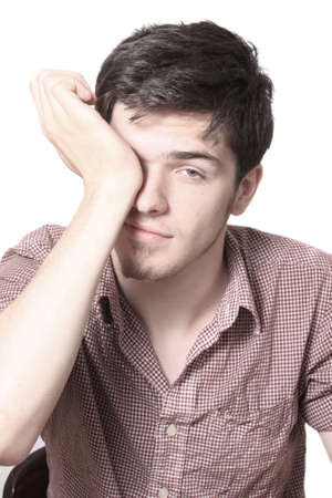 Tired young caucasian man rubbing his eyes on a white background