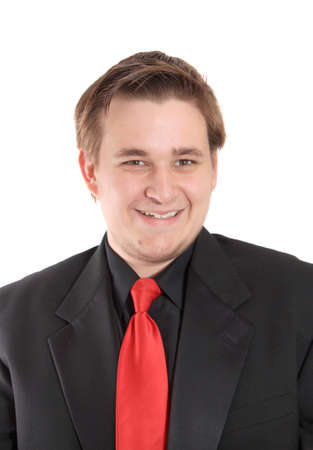 Handsome smiling young man dressed in black formal suit with red tie isolated on a white background