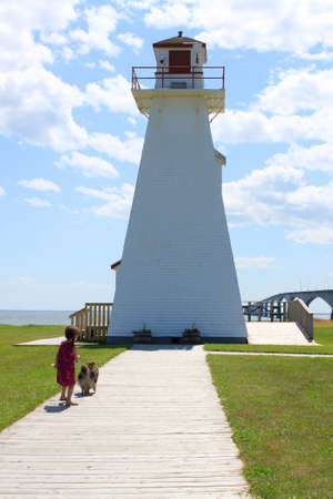 confederation: Little girl walking her Sheltie dog by a lighthouse in Prince Edward Island with the Confederation Bridge in the background