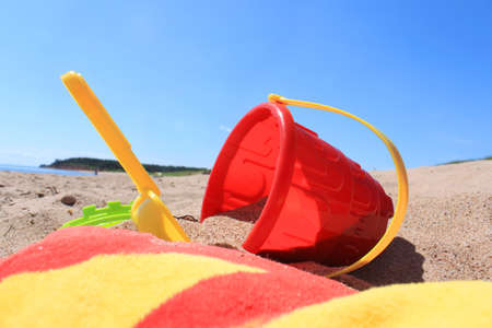 edward: Colorful beach toys and towel in the sandy shores of Panmure Island in Prince Edward Island, Canada