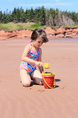 five years old: Llittle girl playing in the sand with toys at Cabot Beach, Prince Edward Island, Canada Stock Photo