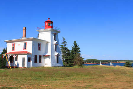 edward: Lighthouse at Rocky Point, Prince Edward Island, Canada under blue skies with sailboats in the background
