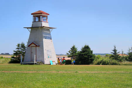 Lighthouse at Cabot Beach with beachgoers in Prince Edward Island, Canada photo