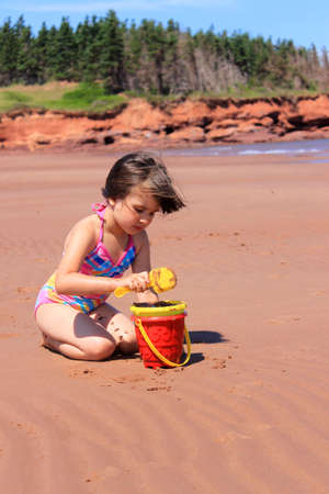 Llittle girl playing in the sand with toys at Cabot Beach, Prince Edward Island, Canada photo