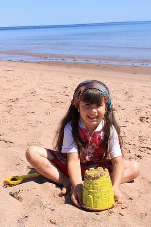 Gelukkig meisje spelen in het zand met speelgoed op Panmure Island strand, Prince Edward Island, Canada Stockfoto