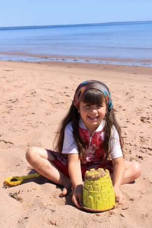 Happy little girl playing in the sand with toys at Panmure Island beach, Prince Edward Island, Canada Foto de archivo