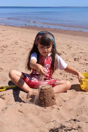 砂再生で玩具と Panmure 島ビーチ、プリンスエド ワード島、カナダでの幸せな女の子 写真素材