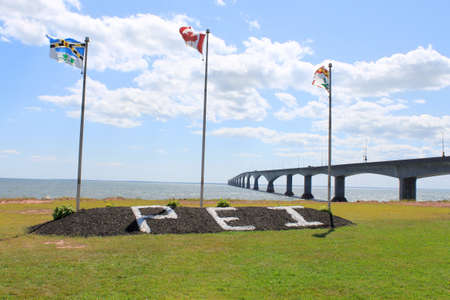 confederation: Confederation Bridge, the entrace to Prince Edward Island from New Brunswick, with flags and sign, in park Stock Photo