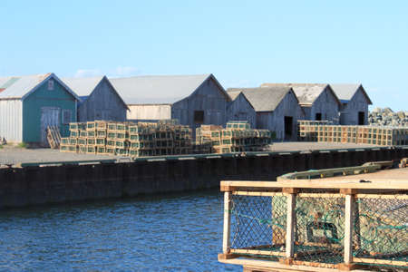 edward: Lobster traps on shore with storage barns  in the background, in Prince Edward Island