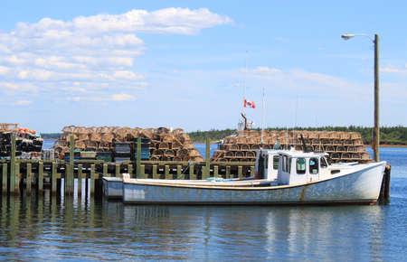 fischerei: Fischerboot am Pier mit Hummer Fallen im Hintergrund in Prince Edward Island, Kanada Lizenzfreie Bilder