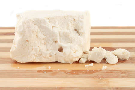 feta cheese: Chunk of Feta Cheese with crumbles on a wooden board Stock Photo