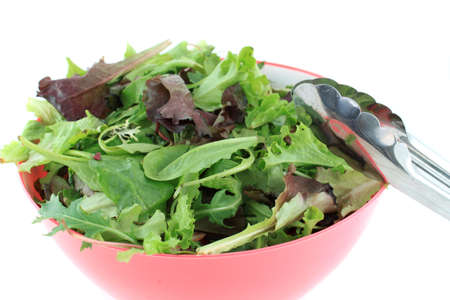 romaine: Mixed greens including aragula, baby spinach and romaine lettuce for a salad with tongs on the side on a white background Stock Photo