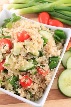 Koude quinoa salade met komkommer, cherry tomaten, groene uien en kruiden