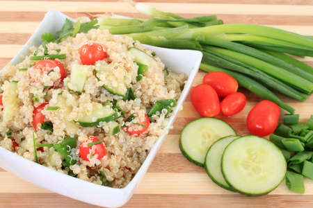 Cold quinoa salad with cucumbers, cherry tomatoes, green onions and herbs photo