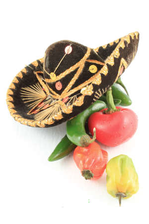 Variety of hot peppers including jalapenos with sombrero on white background photo