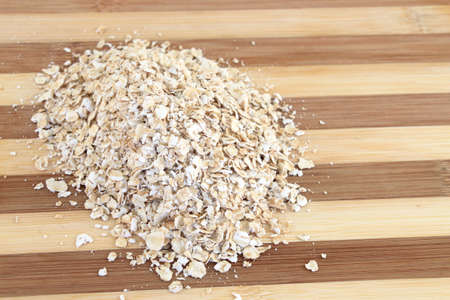 Serving of dry Oatmeal on a wooden board ready for cooking Stock Photo