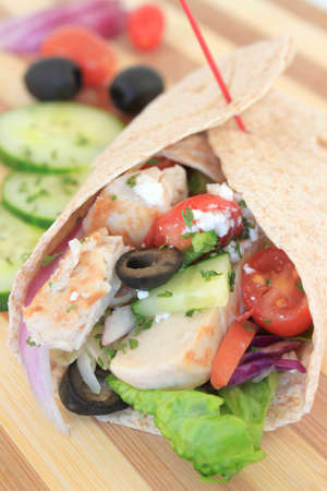 Healthy chicken wrap greek style with fresh vegetables, black olives, feta cheese and herbs  photo