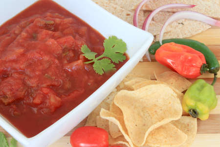 habanero: Bowl of tomato salsa with hot spicy peppers like jalapenos, onions, chips and tortillas for dipping