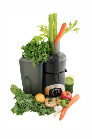 Juicer surrounded by healthy vegetables like carrots, ginger, and kale with fresh made green juice ready to drink