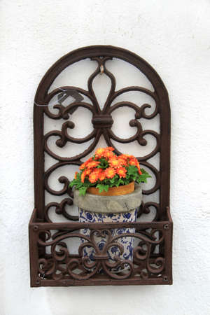 stucco: Decorative iron work flower pot holder with orange blossoms on a white stucco wall background, in Evora, Portugal