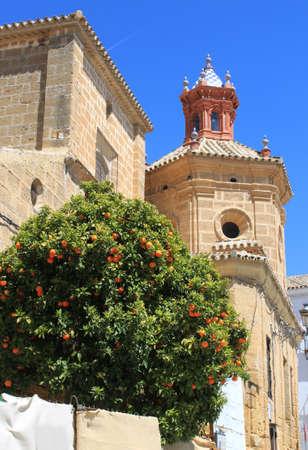 Beautiful church steeple displaying Moorish architecture with orange tree in Osuna, Andalusia, Spain