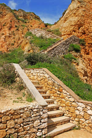 Stairs built in the ochre colored cliffs at Ponte da Piedade in Lagos, Algarve, Portugal, under blue sky 版權商用圖片