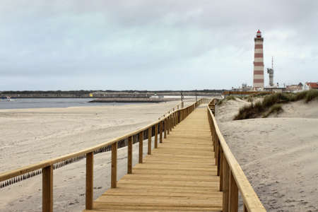 praia: Long wooden boardwalk along the Atlantic Ocean in Praia Barra, Aveiro, Portugal with red striped lighthouse in the background on an overcast day