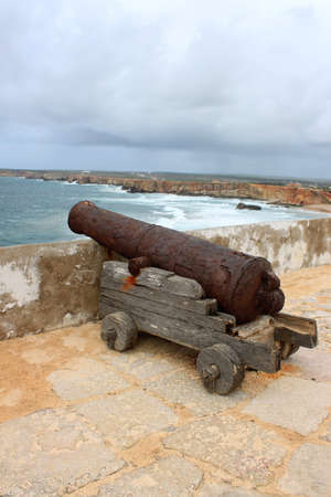 Rugged and rocky cliffs of the Algarve coastline in Sagres, Portugal, on the Atlantic Ocean under dark rainy sky and cannon showing protection