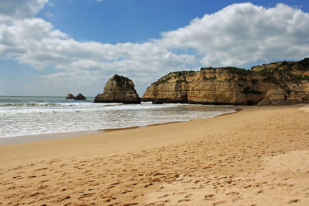 Waves along the golden sandy shored beach and ochre cliffs of Praia da Rocha in Algarve, Portugal