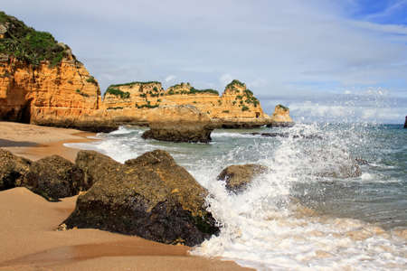 Dona Ana Beach in Lagos with waves splashing on rocks, Algarve, Portugal