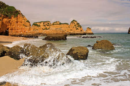 Waves splashing on the rocks of Dona Ana Beach in Lagos, Algarve, Portugal at sunset