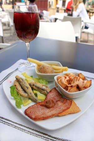 Warme tapas bestaande uit gebakken sardientjes, spek op een tostada, friet met saus en gehaktbal, met een glas sangria, voedsel uit Andalusië, Spanje Stockfoto
