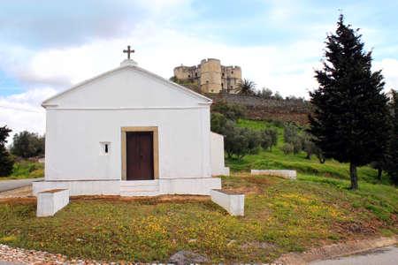 Simple rural church in front of castle in Evoramonte, Alentejo, Portugal Banco de Imagens