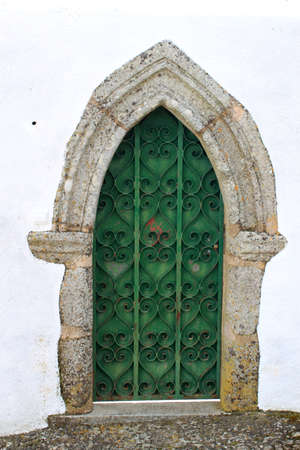 ironwork: Green medieval wooden door with ornate ironwork that goes to a point at the top on a white washed wall Stock Photo