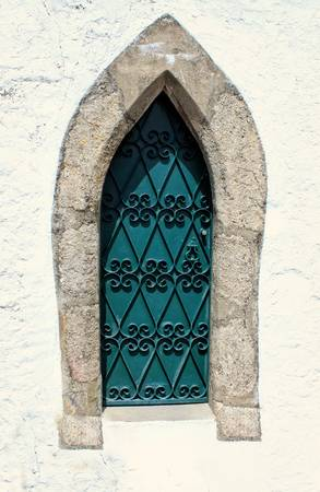 white washed: Green medieval window with ornate ironwork on a white washed wall