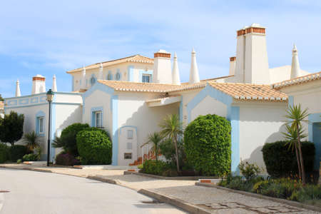 Blue striped white washed houses on a street in the Algarve showing typical chimneys from Portugal 版權商用圖片