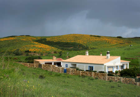 region of algarve: House sits on the hills near Vila do Pispo in South Western part of Portugal in the Algarve region with cloudy dark sky