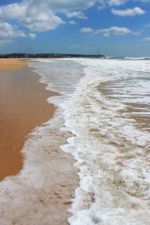 rocha: Seafoam waves along the golden sandy shored beach of Praia da Rocha in Algarve, Portugal