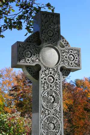 celtic cross: Beautifully decorated stone work on cross during Autumn or Fall time in the largest   cemetery in Canada located in Mount Royal, Montreal Stock Photo