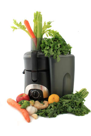 juicer: Juicer surrounded by healthy vegetables like carrots, ginger, and kale ready to make  fresh  juice