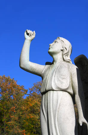 angel cemetery: Statue of Angel looking towards the sky or heaven with arm raised up in faith or hope, at a cemetery in Montreal, Quebec with autumn