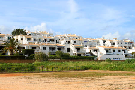 white washed: Beachside white washed houses on a street in the Algarve showing typical chimneys from southern Portugal Stock Photo