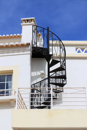 oudoors: Abstract twisty iron staircase outside of a house in Algarve, Portugal