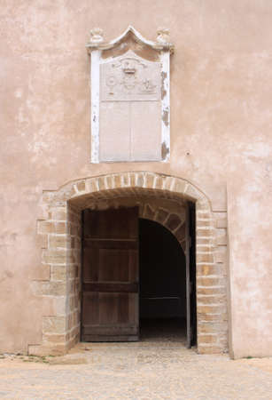Opened wooden door with surrounding brickwork and decorative crest above the door