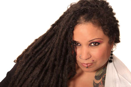 Beautiful ethnic curvaceous woman with long dreadlocks, tattoos and piercings, on a white  Stock Photo