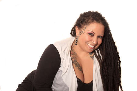 Beautiful ethnic curvaceous woman with long dreadlocks, tattoos and piercings, on a white background