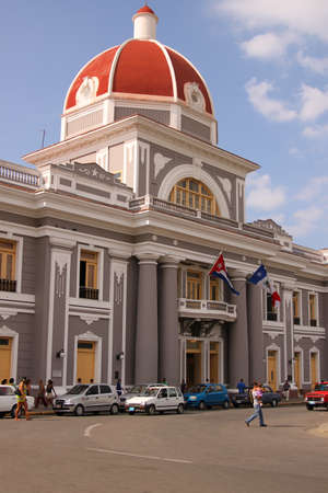 capitolio: CIENFUEGOS, CUBA - FEBRUARY 25, 2014: Architecture along Plaza Jose Marti  with people and traffic going about everyday life in Cienfuegos, Cuba on February 25, 2014 Editorial