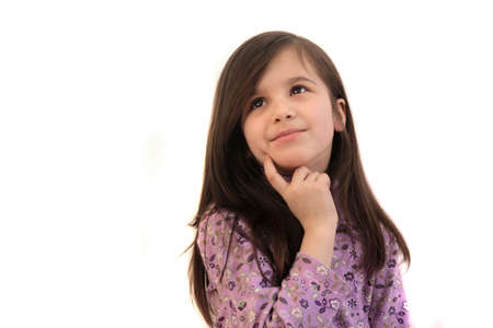 Pretty little brunette 6 year old girl thinking, looking up with finger to face on a white background and copyspace Stock Photo