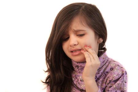 hand held: Cute bambina con la sua mano tesa per il viso con un'espressione dolorosa mostrando il mal di denti
